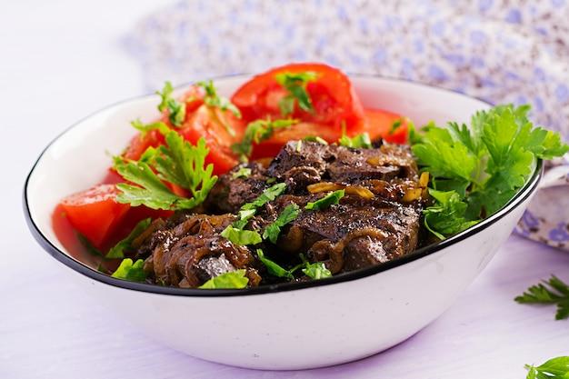 Жареная или жареная говяжья печень с салатом из лука и помидоров, ближневосточная кухня. Premium Фотографии