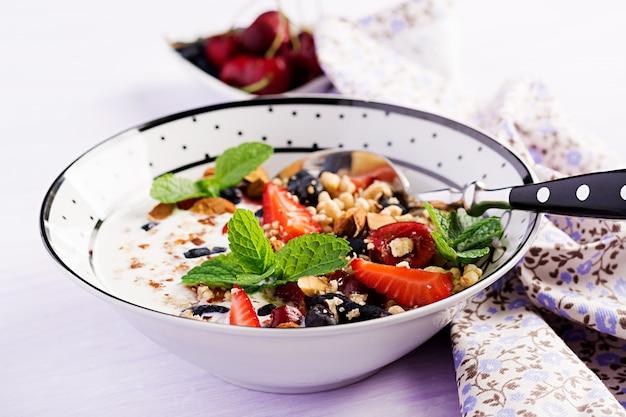 健康的な朝食-グラノーラ、イチゴ、チェリー、スイカズラベリー、ナッツ、ヨーグルトをボウルに Premium写真