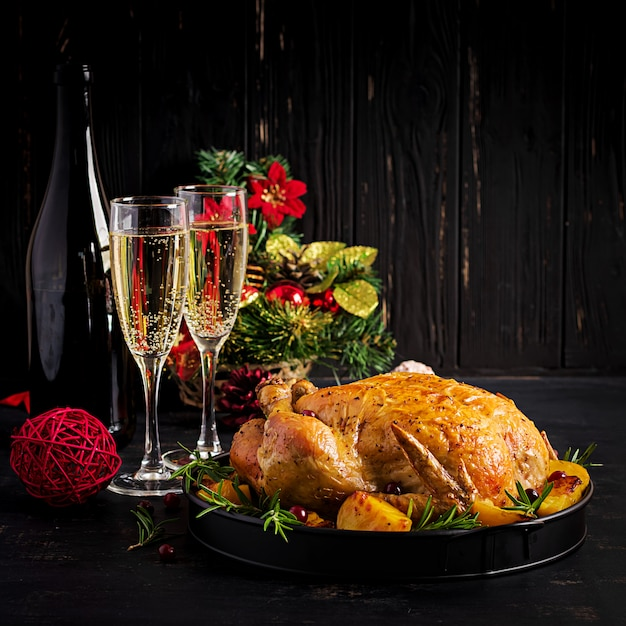 焼き七面鳥または鶏肉。クリスマステーブルには七面鳥が添えられ、明るい見掛け倒しで飾られています。フライドチキン。テーブルセッティング。クリスマスディナー。 Premium写真