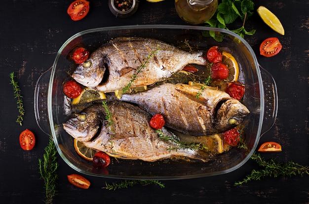 素朴な暗い背景にパンを焼くレモンとハーブ焼き魚ドラド。上面図。魚のコンセプトでヘルシーなディナー。ダイエットときれいな食事 Premium写真