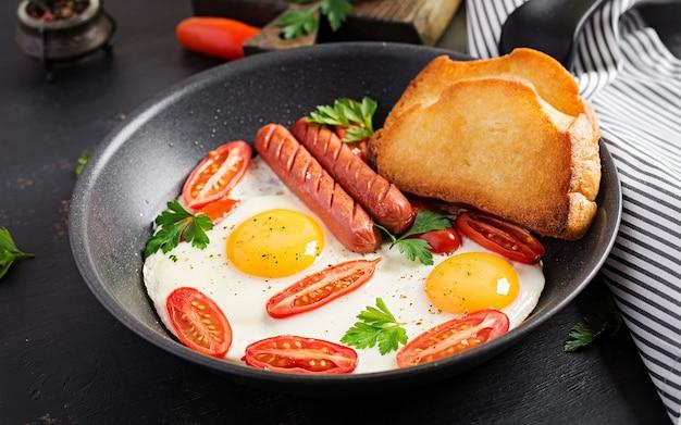イングリッシュブレックファースト-目玉焼き、トマト、ソーセージ、トースト。上面図 Premium写真