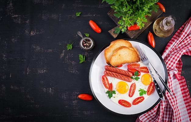 イングリッシュブレックファースト-目玉焼き、トマト、ソーセージ、トースト。上面図、オーバーヘッド Premium写真
