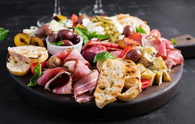 ハム、生ハム、サラミ、ブルーチーズ、モッツァレラチーズとペストとオリーブの前菜盛り合わせ。 Premium写真