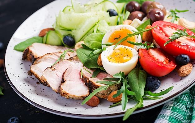 Кетогенная диета. кето бранч. вареное яйцо, стейк из свинины и маслины, огурец, шпинат, сыр бри, орехи и помидор. Premium Фотографии