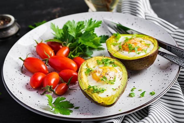 卵と新鮮なサラダで焼いたアボカド。ベジタリアン料理。ケトジェニックダイエット。ケトフード Premium写真