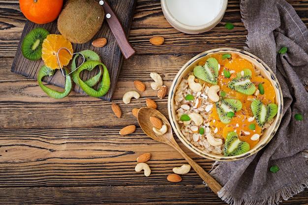 Вкусная и полезная овсяная каша с фруктами, ягодами и орехами. здоровый завтрак. фитнес-питание. правильное питание. вид сверху Premium Фотографии