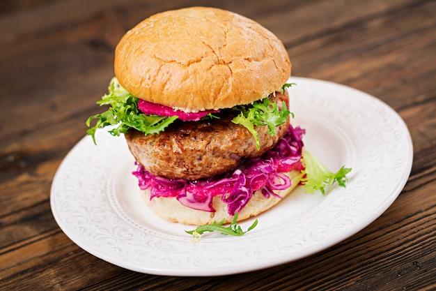 ジューシーなハンバーガー、赤キャベツ、ピンクソースがけのサンドイッチハンバーグ 無料写真
