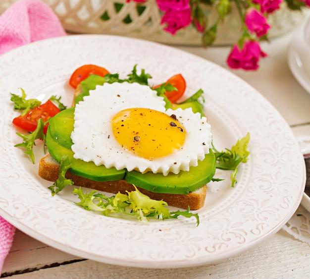 バレンタインデーの朝食-ハート、アボカド、新鮮な野菜の形をした目玉焼きのサンドイッチ。一杯のコーヒー。イングリッシュブレックファースト。 Premium写真