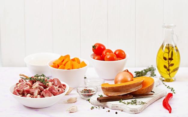 Ингредиенты для приготовления куриных сердечек с тыквой и помидорами в томатном соусе. гарнир подается с отварным рисом. Premium Фотографии