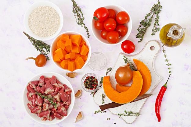 Ингредиенты для приготовления куриных сердечек с тыквой и помидорами в томатном соусе. гарнир подается с отварным рисом. квартира лежала. вид сверху. Premium Фотографии