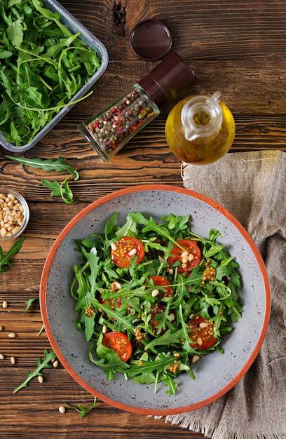食事メニュー。ビーガン料理。ルッコラ、トマト、松の実のヘルシーサラダ。平干し。上面図 無料写真
