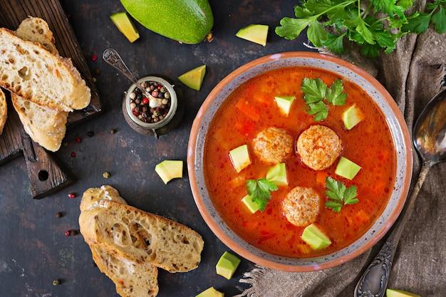 ミートボールと野菜のスパイシートマトスープ。アボカドとパセリを添えて。健康的な夕食。上面図 Premium写真