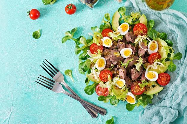 鶏レバー、アボカド、トマト、ウズラの卵の温かいサラダ。健康的な夕食。食事メニュー。平干し。上面図 無料写真