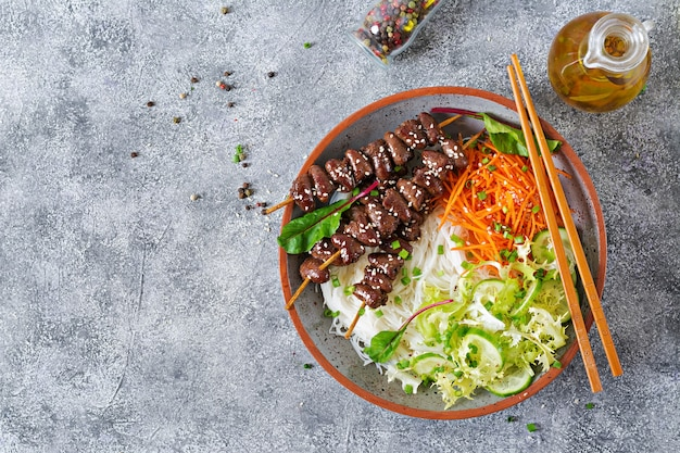 Куриные сердечки в остром соусе с лапшой и овощным салатом. здоровая пища. вид сверху Premium Фотографии
