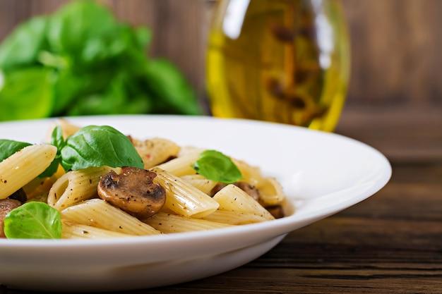 木製テーブルの上の白いボウルにキノコのベジタリアン野菜パスタペンネ。ビーガンフード 無料写真
