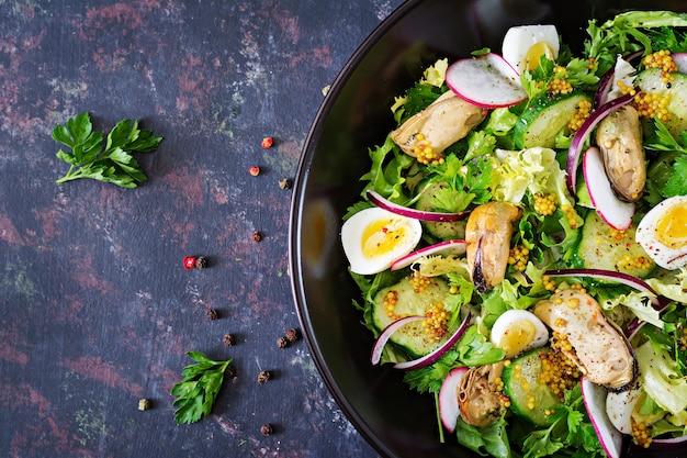 ムール貝、ウズラの卵、キュウリ、大根、レタスの栄養サラダ。健康食品。シーフードサラダ。上面図。平干し。 無料写真