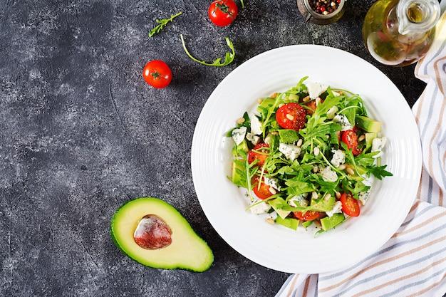 トマト、ブルーチーズ、アボカド、ルッコラ、松の実の栄養サラダ。 無料写真