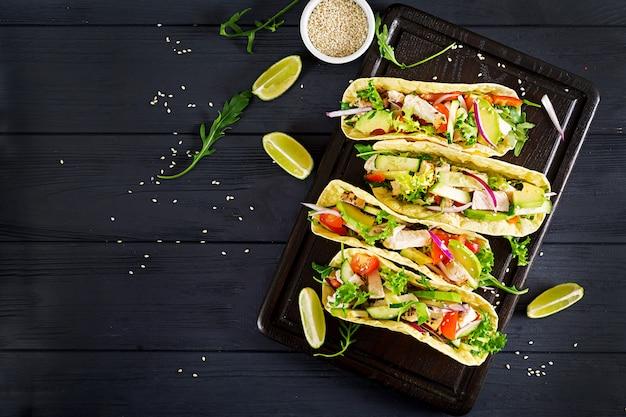 鶏肉、アボカド、トマト、キュウリ、赤玉ねぎのメキシコのタコス。 Premium写真