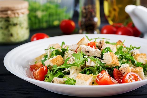 Полезный куриный салат цезарь на гриле с помидорами, сыром и гренками. Premium Фотографии