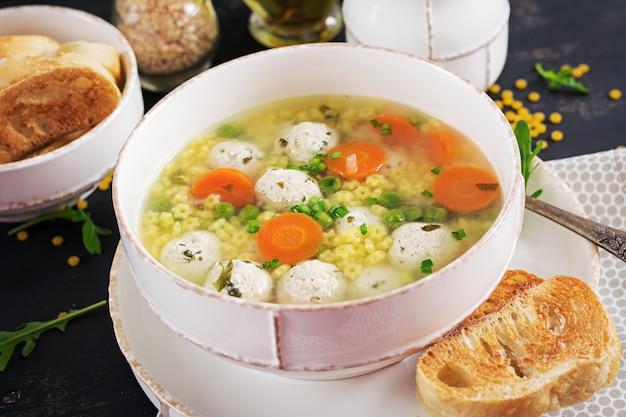 イタリアのミートボールスープと黒いテーブルの上のボウルにステリーネパスタ。栄養スープ。ベビーメニュー。おいしい食べ物。 無料写真