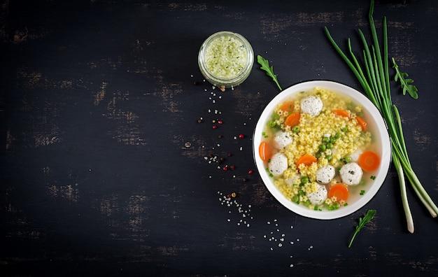 黒いテーブルの上のボウルにイタリアのミートボールスープとステリーングルテンフリーパスタ。 無料写真