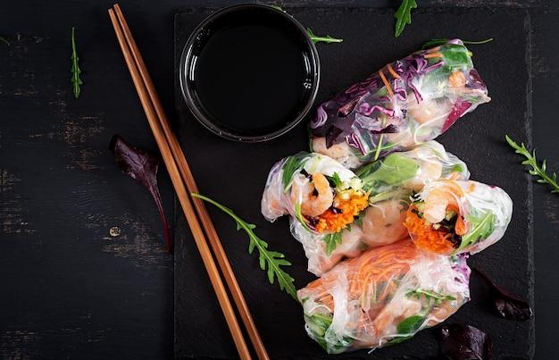Вегетарианские вьетнамские блинчики с начинкой с пряными креветками, креветками, морковью, огурцом, красной капустой и рисовой лапшой. Premium Фотографии