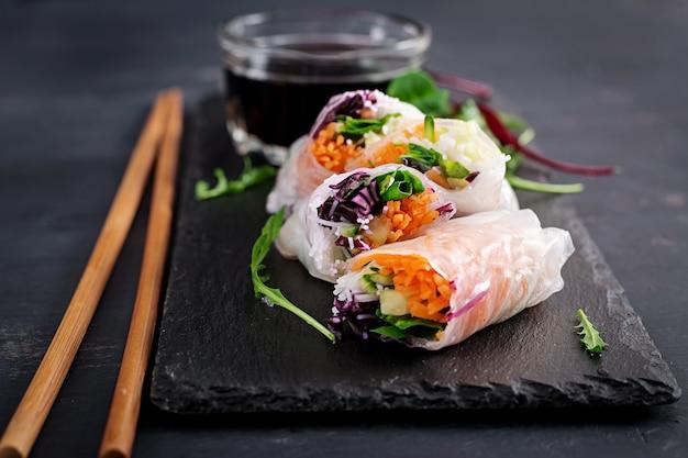 Вегетарианские вьетнамские блинчики с начинкой с острым соусом, морковью, огурцом, красной капустой и рисовой лапшой. Premium Фотографии