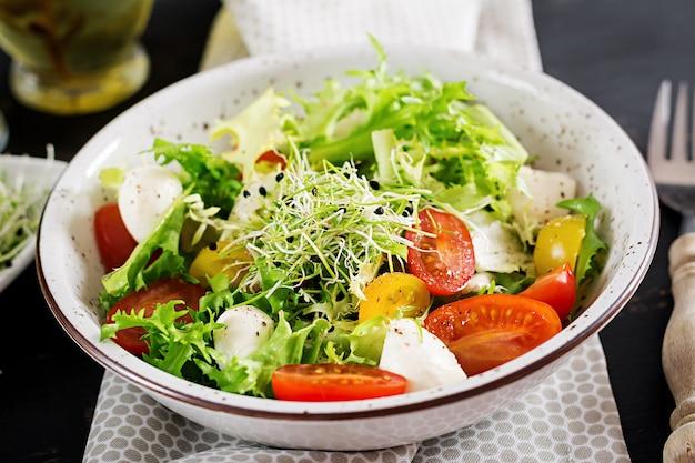 チェリートマト、モッツァレラチーズ、レタスのベジタリアンサラダ。 無料写真