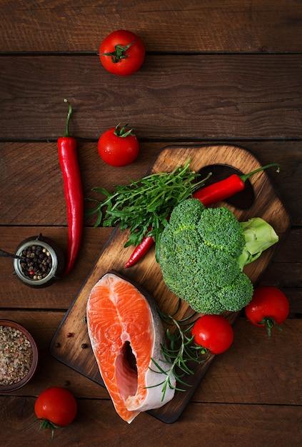 Сырой стейк из лосося и овощей для приготовления пищи на деревянный стол в деревенском стиле. вид сверху Бесплатные Фотографии
