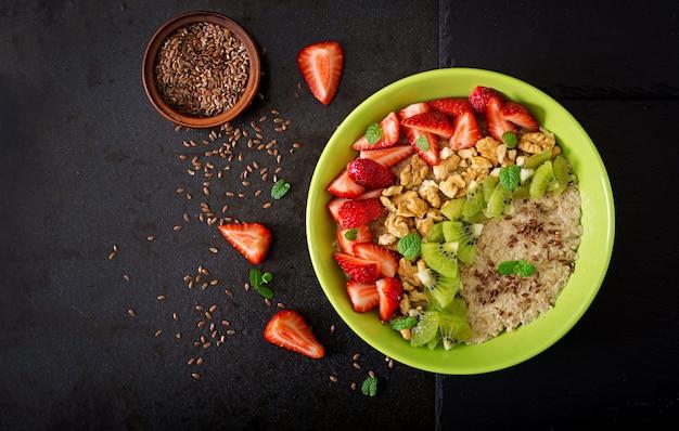 ベリー、ナッツ、亜麻の種子が入ったおいしいヘルシーなオートミールポリッジ。健康的な朝食。フィットネス食品。適切な栄養。平干し。上面図 Premium写真
