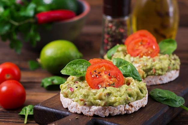 Здоровый завтрак. сэндвич хрустящий хлеб с гуакамоле и помидорами на деревянном столе. Бесплатные Фотографии