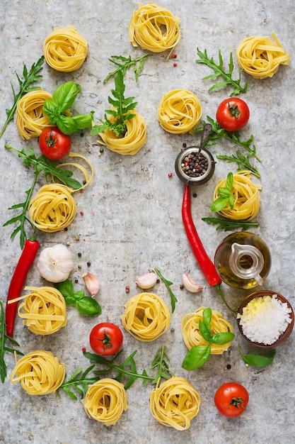 Паста тальятелле, гнездо и ингредиенты для приготовления пищи (помидоры, чеснок, базилик, перец чили). вид сверху Бесплатные Фотографии