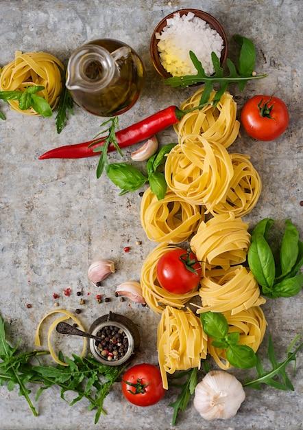 パスタタリアテッレの巣と料理の材料(トマト、ニンニク、バジル、チリ)。上面図 Premium写真