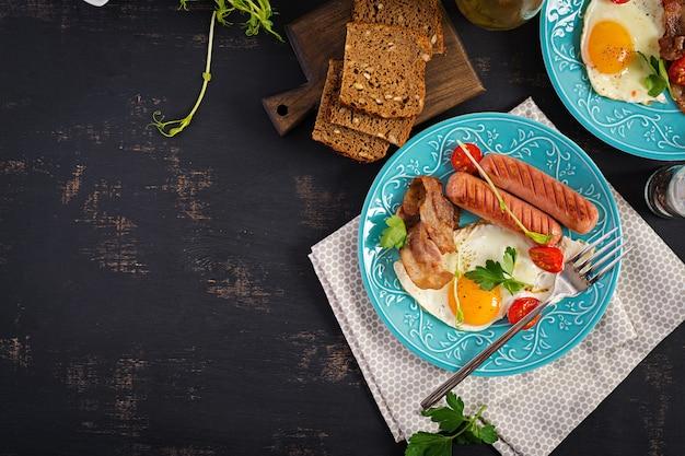 イングリッシュブレックファースト-目玉焼き、トマト、ソーセージ、ベーコン。上面図 Premium写真