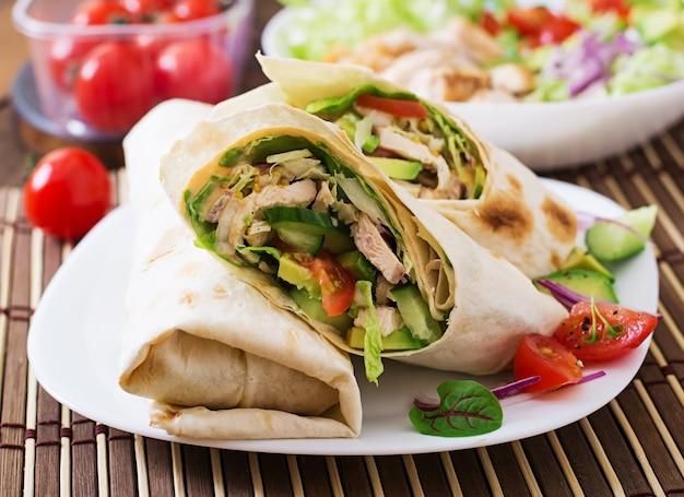 皿に鶏肉と新鮮な野菜を巻いた新鮮なトルティーヤ Premium写真