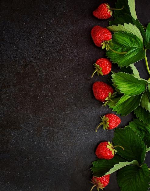 熟したイチゴと黒の背景の葉。上面図 無料写真