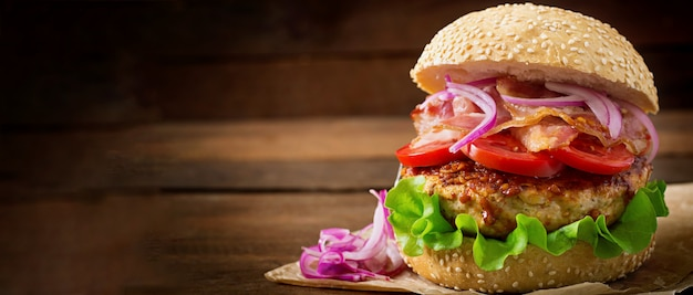 Большой бутерброд - гамбургер с говядиной, красным луком, помидорами и жареным беконом. Бесплатные Фотографии