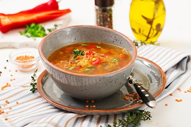 赤レンズ豆、肉、赤パプリカ、香ばしいタイムの食欲をそそるスープ Premium写真