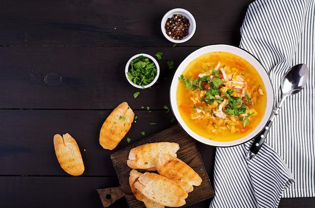 テーブルの上の鶏肉と野菜のクローズアップと赤レンズ豆のスープ。健康食品。上面図 Premium写真