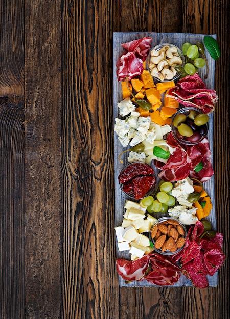 Антипасто блюдо с беконом, вяленым мясом, колбаса, голубой сыр и виноград на деревянном столе. вид сверху Premium Фотографии