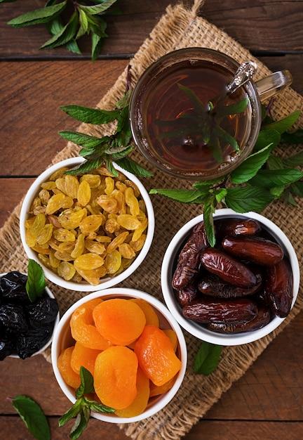 Смешайте сухофрукты (плоды финиковой пальмы, чернослив, курагу, изюм) и орехи, а также традиционный арабский чай. рамадан (рамазан) еда. вид сверху Бесплатные Фотографии