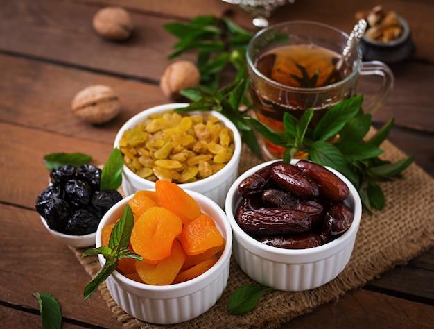 ドライフルーツ(ナツメヤシフルーツ、プルーン、ドライアプリコット、レーズン)とナッツ、および伝統的なアラビア茶を混ぜます。ラマダン(ラマザン)料理。 無料写真