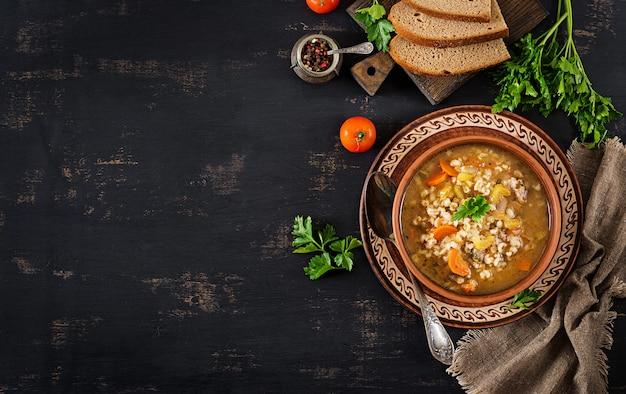 ニンジン、トマト、セロリ、暗い背景に肉と大麦のスープ。上面図。 無料写真