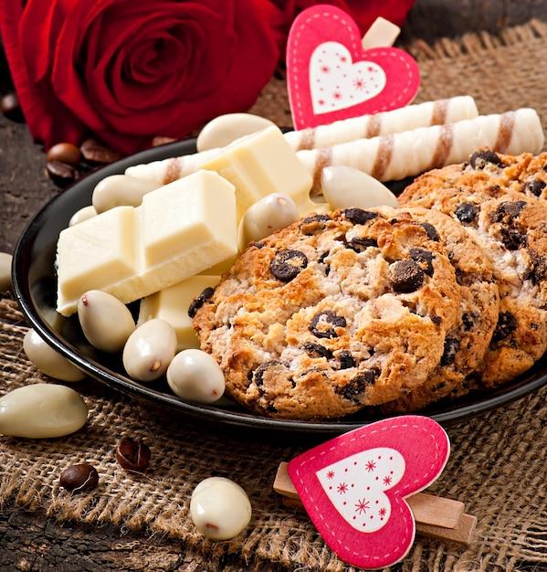 Белый шоколад, миндаль и печенье на деревянной поверхности Бесплатные Фотографии