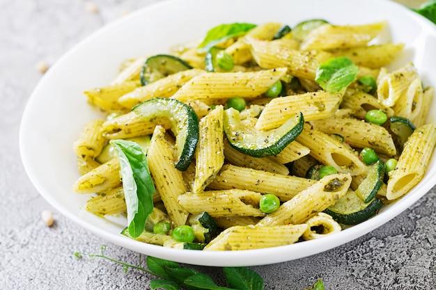 ペストソース、ズッキーニ、グリーンピース、バジルのペンネパスタ。イタリア料理。 無料写真