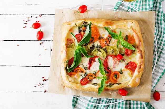 Моцарелла, помидоры, базилик пикантный пирог на белом деревянном столе. вкусная еда, закуска в средиземноморском стиле. вид сверху. плоская планировка Бесплатные Фотографии