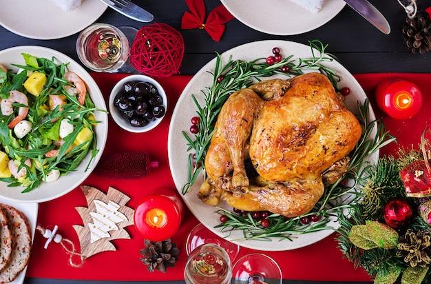焼き七面鳥。クリスマスディナー。クリスマステーブルには七面鳥が添えられ、明るい見掛け倒しとキャンドルで飾られています。フライドチキン、テーブル。家族との夕食。上面図 無料写真