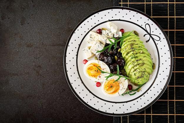 スナックまたは健康的な朝食-黒い表面にブルーチーズ、アボカド、ゆで卵、オリーブのプレート。上面図 無料写真