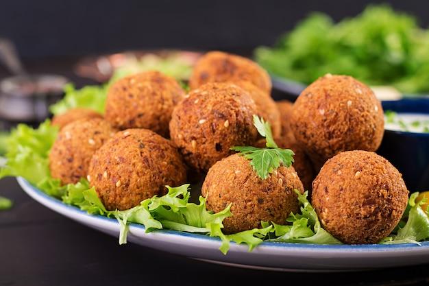 Фалафель, хумус и пита. ближневосточные или арабские блюда на темном столе Premium Фотографии