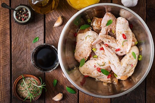 Сырые маринованные куриные крылышки, приготовленные в азиатском стиле с медом, чесноком, соевым соусом и зеленью. вид сверху Бесплатные Фотографии
